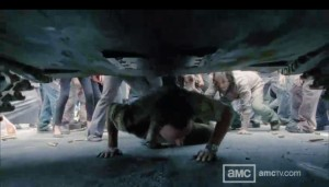 Rick crawls under a tank to escape the zombies
